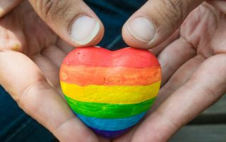 Hands holding a heart shaped rock painted with rainbow colors