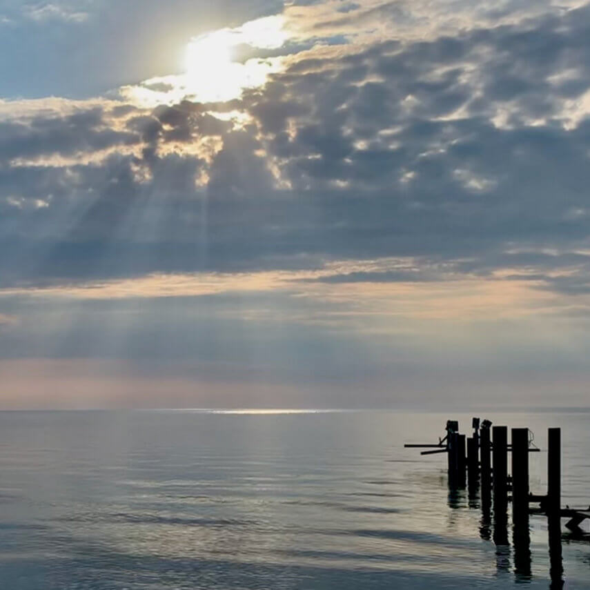 Sun shining through the clouds over water, with a pier and birds